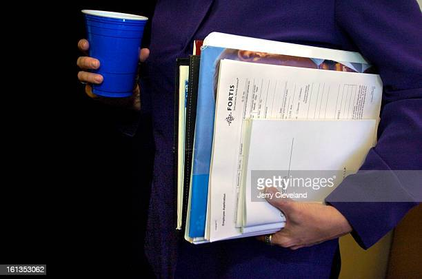 DENVER COLO JUNE 13 2005 Kim Sporrer<cq> holds her employee handbook and other materials during her first day on the job at Linhart McClain Finlon...