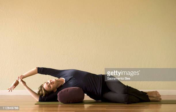 Kim Wagaman demonstrates a side stretch with a bolster at Yoga Solution in Sacramento California Monday December 14 2009
