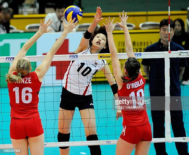 Kim YeonKoung of South Korea spikes the ball through Jennifer Hinze and Lauren O'Reilly of Canada during their first round match of the World Women's...