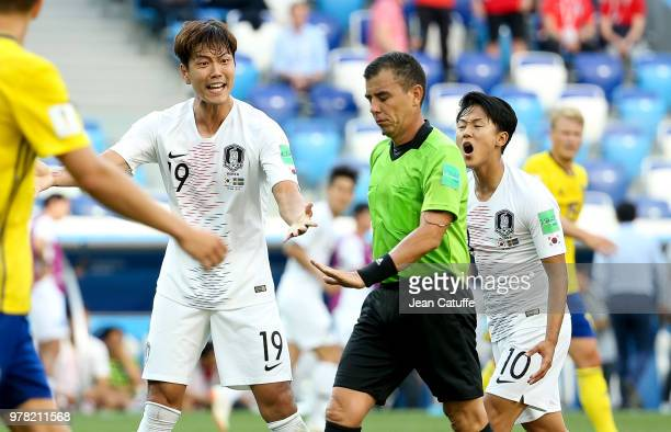 Kim Younggwon and Lee Seungwoo of South Korea contest the decision of referee Joel Aguilar of Salvador during the 2018 FIFA World Cup Russia group F...