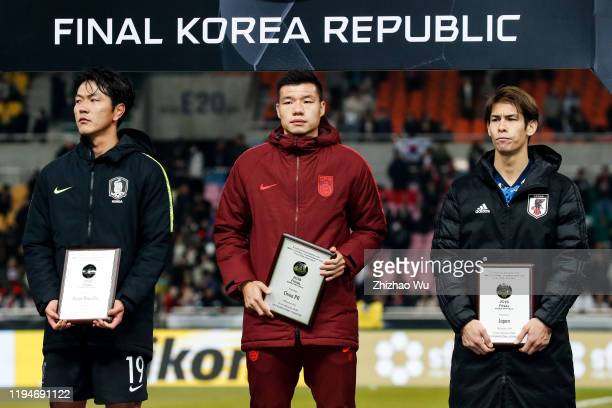 Kim Younggwon of South Korea Mei Fang and Sasaki Sho of Japan attend the award ceremony after the EAFF E-1 Football Championship match between South...