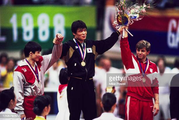 Kim Young-Nam of South Korea celebrates his gold medal with silver medallist Daulet Turlykhanov of the Soviet Union and bronze medallist Jozef Tracz...