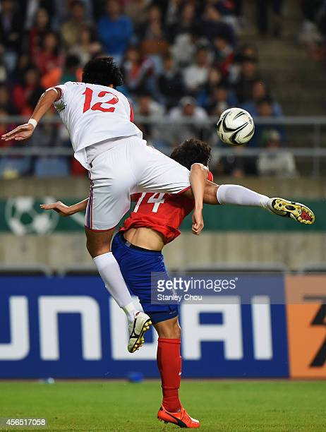 Kim Younguk of South Korea and Ri Yongjik of North Korea compete for the ball during the Football Men's Gold Medal match between South Korea and...