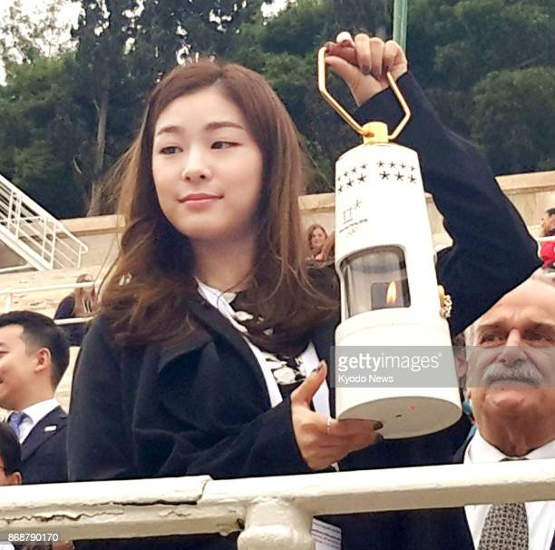 Kim Yu Na the 2010 Vancouver Olympic women's figure skating gold medalist holds the Olympic flame in a lantern at the Panathenaic Stadium in Athens...