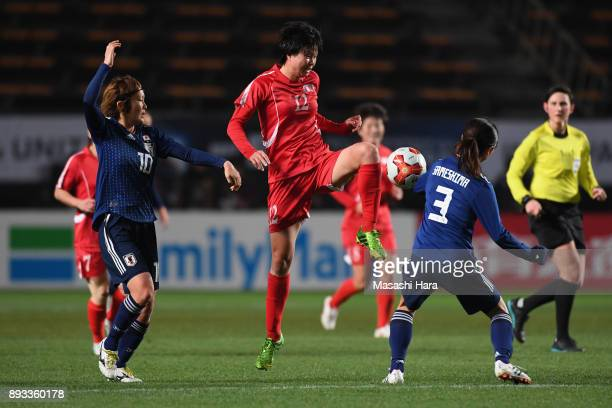 Kim Yun Mi of North Korea controls the ball under pressure of Mizuho Sakaguchi and Aya Sameshima of Japan during the EAFF E1 Women's Football...
