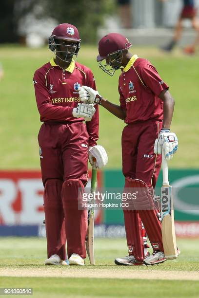 Kimani Melius and Keagan Simmons of the West Indies bump fists in between overs during the ICC U19 Cricket World Cup match between New Zealand and...