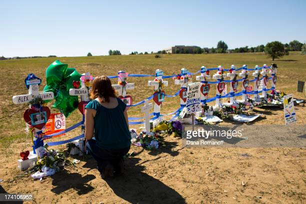 Kimber Avra sits by a cross honoring her friend Micayla Medek at a remembrance ceremony July 20 2013 in Aurora Colorado The ceremony marks the one...