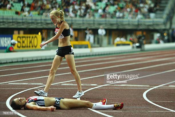 Kimberley Smith of New Zealand walks past Jo Pavey of Great Britain as she lays exhausted after competing in the Women's 10000m final on day one of...