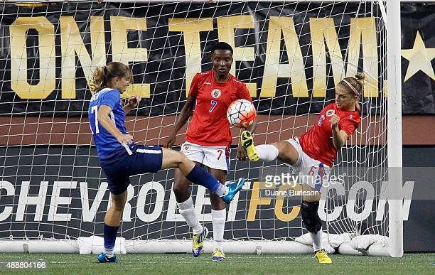 Kimberly Boulos of Haiti kicks the ball away from the goal against Tobin Heath of the United States as goalie Roselord Borgella of Haiti looks on...