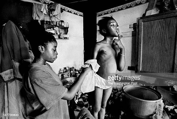 FILE Kimberly Collins gives her sister Tiara Collins a sponge bath in their home in Bayview Virginia on August 1 1998 There is no indoor plumbing or...
