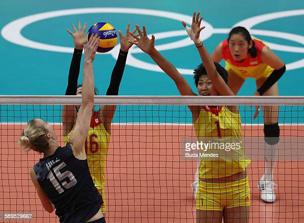 Kimberly Hill of the United States spikes the ball against Xia Ding and Xinyue Yuan during the women's qualifying volleyball match between the United...