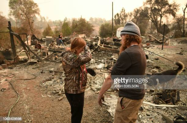 Kimberly Spainhower and her husband Ryan Spainhower weep while searching through the ashes of their burned home in Paradise California on November 18...