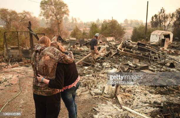 Kimberly Spainhower hugs her daughter Chloe while her husband Ryan Spainhower searches through the ashes of their burned home in Paradise California...