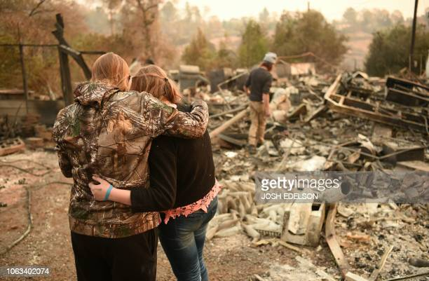 Kimberly Spainhower hugs her daughter Chloe while her husband Ryan Spainhower searches through the ashes of their burned home in Paradise, California...