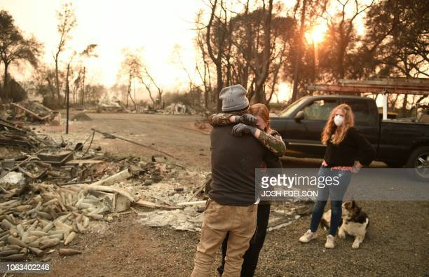 TOPSHOT Kimberly Spainhower hugs her husband Ryan Spainhower while their daughter Chloe Spainhower looks on at the burned remains of their home in...