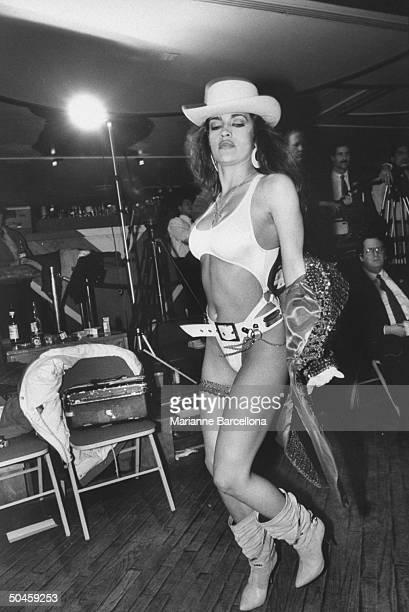 Kimberly woman boxer of Billy Deans Foxy Boxing Revue dressed in cutout bathing suit cowboy boots hat seen removing jacket before fight Great...
