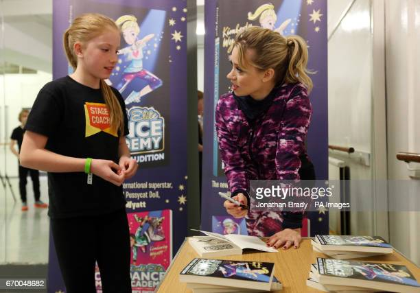 Kimberly Wyatt signs a copy of her new book 'Billie's Big Audition' for eleven year old Maddie Creenan from Croydon during a launch event held at...