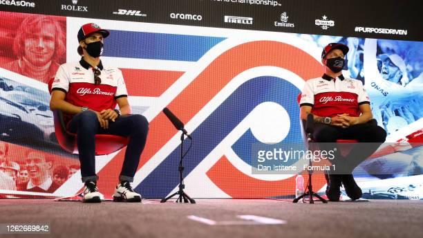 Kimi Raikkonen of Finland and Alfa Romeo Racing and Antonio Giovinazzi of Italy and Alfa Romeo Racing talk in the Drivers Press Conference during...