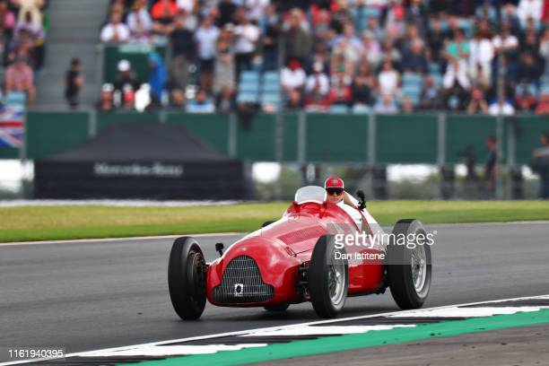 Kimi Raikkonen of Finland and Alfa Romeo Racing drives an old Alfa Romeo on track for the drivers parad before the F1 Grand Prix of Great Britain at...