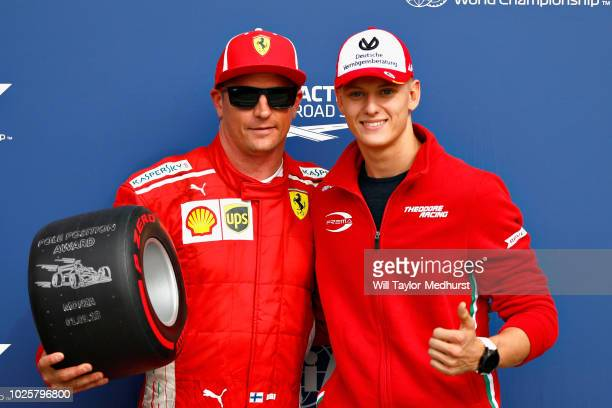 Kimi Raikkonen of Finland and Ferrari is presented with the Pirelli Pole Position trophy by Mick Schumacher in parc ferme during qualifying for the...