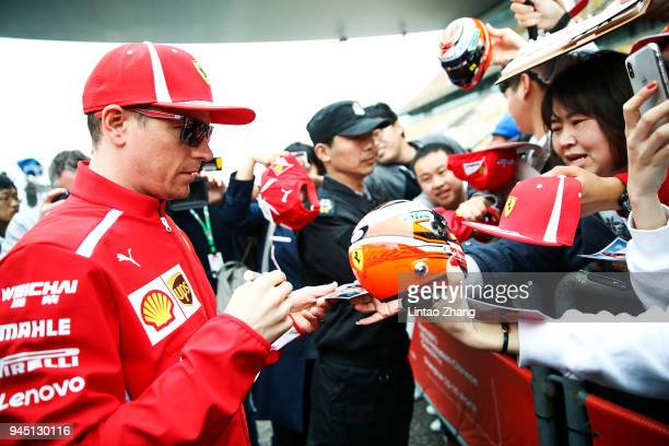 Kimi Raikkonen of Finland and Ferrari signs autographs for fans during the Formula One Grand Prix of China at Shanghai International Circuit on April...