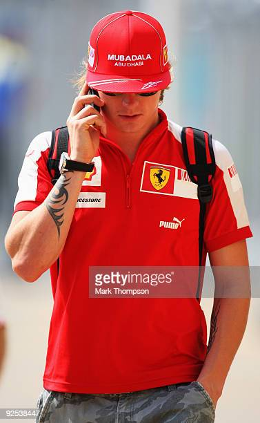 Kimi Raikkonen of Finland and Ferrari talks on the phone in the paddock before practice for the Abu Dhabi Formula One Grand Prix at the Yas Marina...