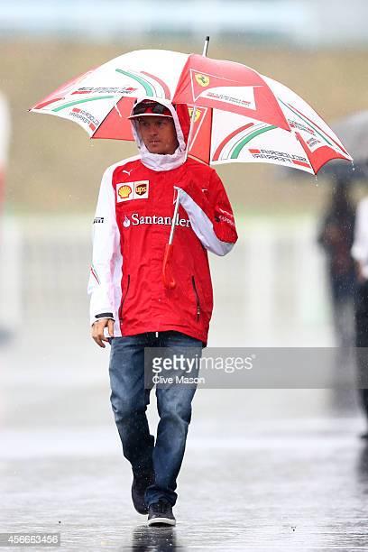 Kimi Raikkonen of Finland and Ferrari walks across a wet paddock prior to the Japanese Formula One Grand Prix at Suzuka Circuit on October 5 2014 in...