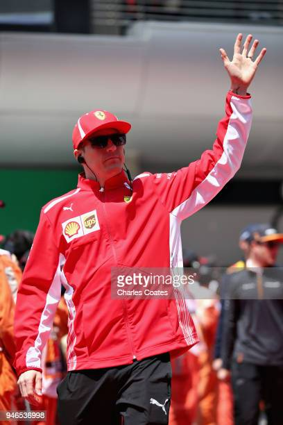 Kimi Raikkonen of Finland and Ferrari waves to the fans on the drivers parade before the Formula One Grand Prix of China at Shanghai International...
