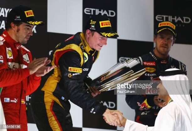 Kimi Raikkonen of Finland and Lotus celebrates on the podium after winning the Abu Dhabi Formula One Grand Prix at the Yas Marina Circuit on November...