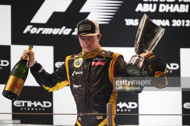 Kimi Raikkonen of Finland and Lotus celebrates on the podium after winning the Abu Dhabi Formula One Grand Prix at the Yas Marina Circuit on November...