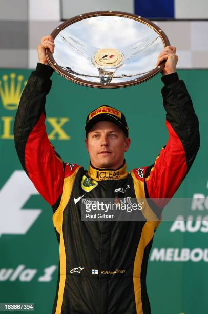 Kimi Raikkonen of Finland and Lotus celebrates on the podium after winning the Australian Formula One Grand Prix at the Albert Park Circuit on March...