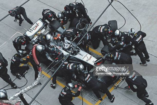 Kimi Raikkonen of Finland driver of the West McLaren MercedesMcLaren MP419 Mercedes V10 is surrounded by mechanics as he makes a pit stop for new...