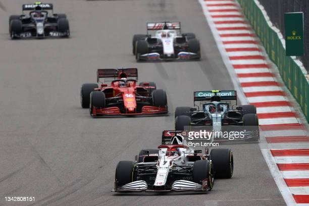 Kimi Raikkonen of Finland driving the Alfa Romeo Racing C41 Ferrari leads Sebastian Vettel of Germany driving the Aston Martin AMR21 Mercedes during...