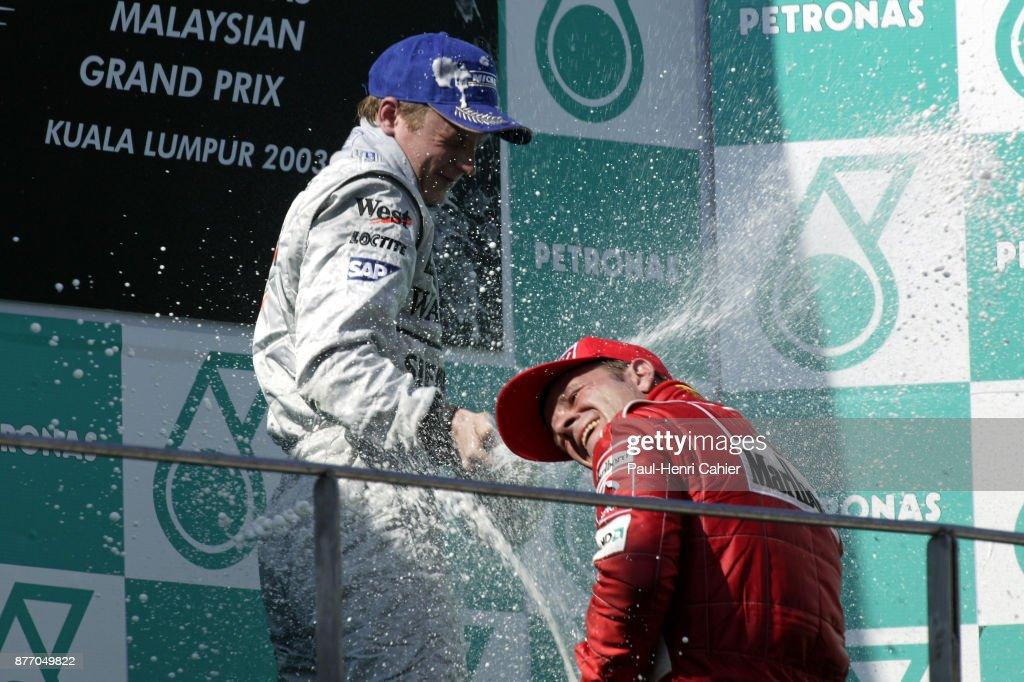 Kimi Raikkonen, Rubens Barrichello, Grand Prix of Malaysia, Sepang International Circuit, 23 March 2003. Kimi Raikkonen on the winners podium with Rubens Barrichello, after winning his first ever Formula One race, the 2003 Malaysian Grand Prix.