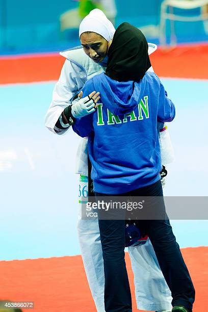 Kimia Alizadeh Zenoorin of Iran celebrates with her coach after beating Yulia Turutina of Russia in the Taekwondo Women's 63kg final match on day...