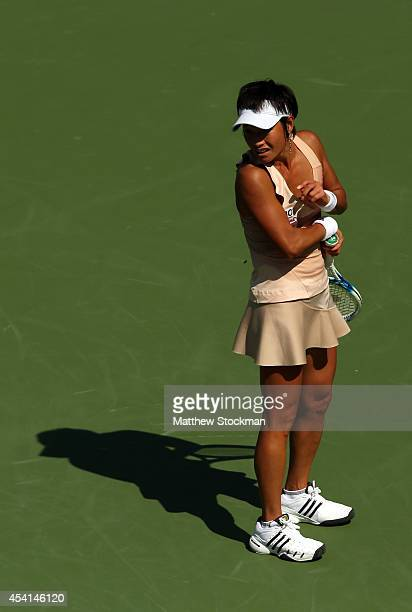 Kimiko DateKrumm of Japan reacts to a honey bee while playing against Venus Williams of the United States during her women's singles first round...