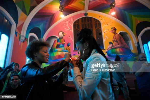 Kimm Miller left from Lakewood lights a pipe for Andrea Camp right from Chicago as they participate in 4/20 celebration services at the International...