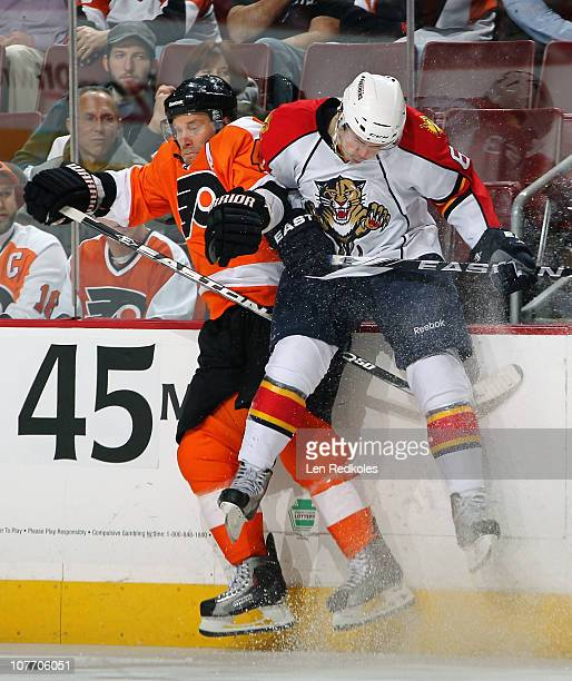 Kimmo Timonen of the Philadelphia Flyers is checked into the boards by Evgeny Dadonov of the Florida Panthers on December 20 2010 at the Wells Fargo...