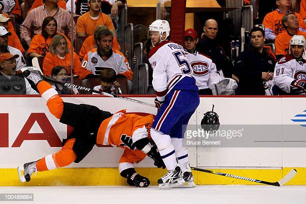 Kimmo Timonen of the Philadelphia Flyers loses his helmet while getting checked by Benoit Pouliot of the Montreal Canadiens in Game 5 of the Eastern...