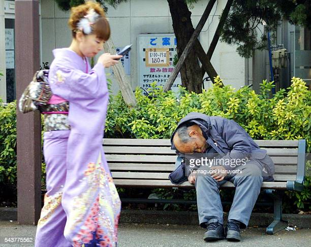 A kimono clad woman talking on her cellphone passes in front of a homeless man during a comingofage day ceremony in Tokyo