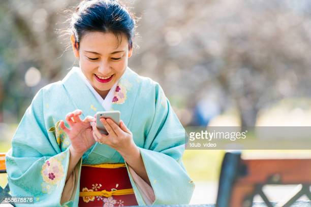 kimono lady using a phone - tdub_video stock pictures, royalty-free photos & images