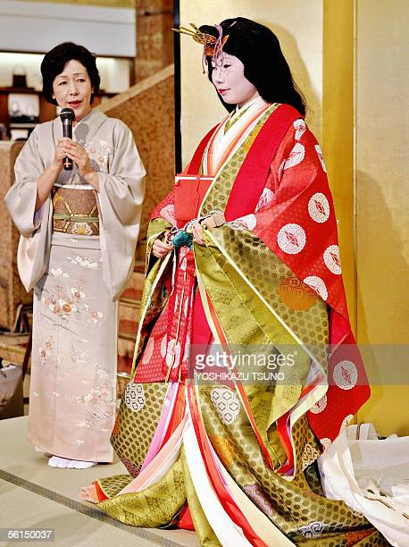 Kimono seamstress Mikami Kazuko explains the details of an ancient Japanese formal court ensemble called a junihitoe on a model for a kimono show at...