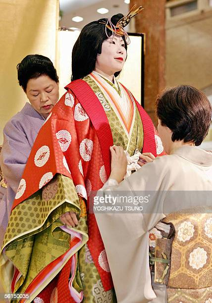 Kimono seamstresses put an ancient Japanese formal court ensemble called a junihitoe on a model for a kimono show at Tokyo's Mitsukoshi department...