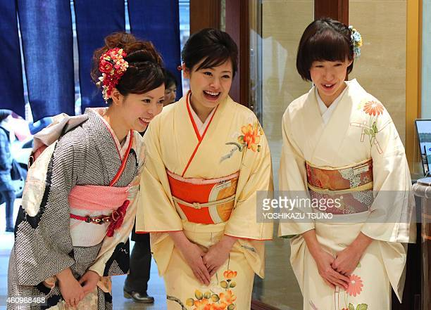 Kimonoclad sales clerks bow and smile to greet New Year's shoppers as they rush into a department store to buy 'lucky bags' containing items worth...