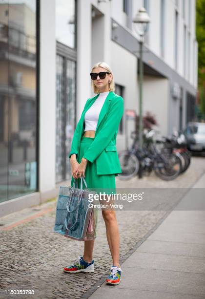 Kimyana Hachmann is seen wearing see through Chanel bag Chanel shoes white cropped shirt green pleated skirt and blazer Celine sunglasses on May 18...