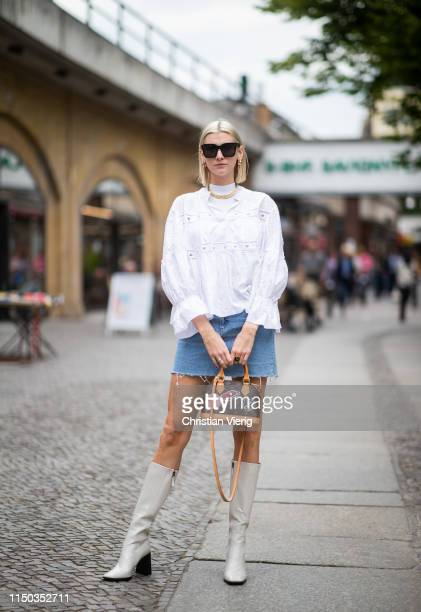 Kimyana Hachmann is seen wearing white blouse Chloe Louis Vuitton bag Celine sunglasses vintage denim skirt white boots on May 18 2019 in Berlin...