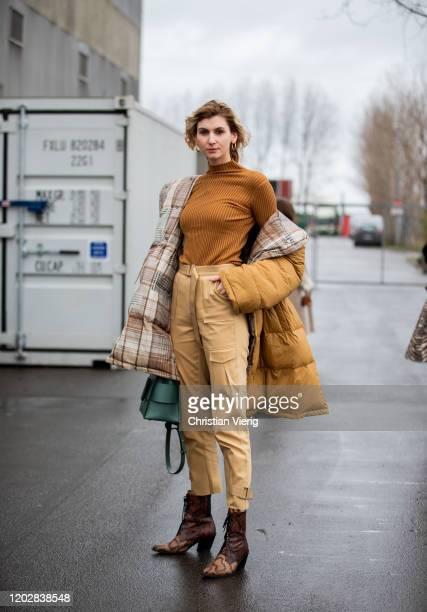 Kimyana Hachmann seen wearing beige pants, coat, knit, Boyy bag, boots with snake print outside Holzweiler during Copenhagen Fashion Week...