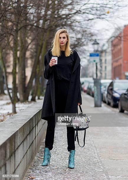 Kimyana Hachmann wearing a black Zara jumpsuit Hermes coat Mai Piu Senza ankle boots Love Moschino bag during the MercedesBenz Fashion Week Berlin...