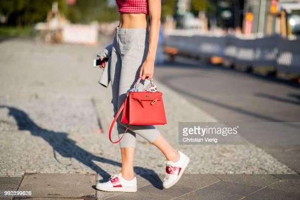 Kimyana Hachmann wearing grey cropped pants red Hermes bag grey jacket cropped top is seen outside Dawid Tomaszewski during the Berlin Fashion Week...