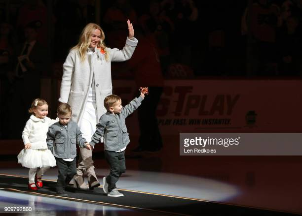 Kina Lamarche Lindros children Sophie Carl and Ryan walk into the ice surface for the Eric Lindros retirement number ceremony prior to a NHL game...